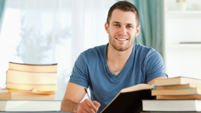 male student smiling and working in textbooks