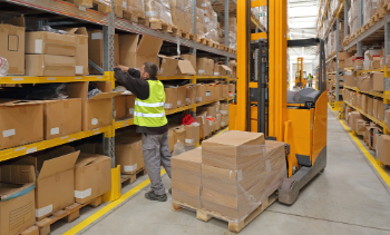 male supply chain worker loading product into shelves in warehouse