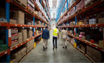 supply chain management walking through warehouse