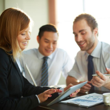 Portrait of smart businesswoman showing her partners something in touchpad at meeting