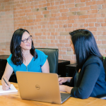 Two female legal assistants talking