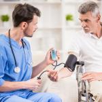 male nurse checking a patient's blood pressure