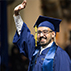 Photo of student waving at crowd during commencement ceremony