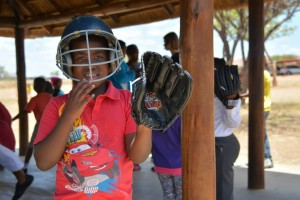 Kid with baseball helmet and glove on