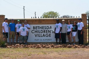 Baseball Miracles team in front of Bethesda Children's Village sign
