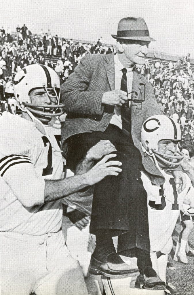 """Coach A.C. """"Scrappy"""" Moore being carried by football players"""