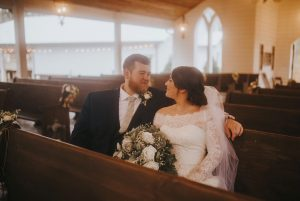 Sydney and Casey in a pew of the wedding chapel, gazing adoringly at each other in wedding gown and tux