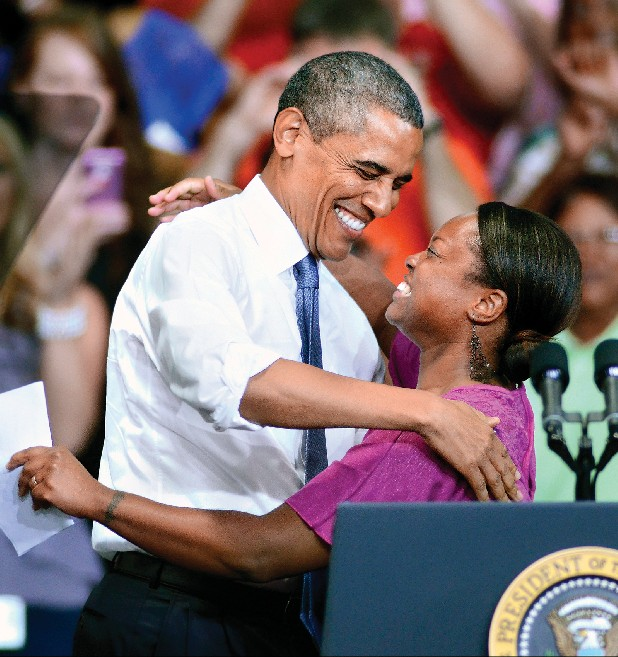 UTC alumna Lydia Flanders hugs President Barack Obama during his visit to the Amazon facility in Chattanooga.
