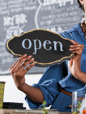 Woman in beauty salon with open sign