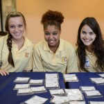 3 girls manning name badge table at Freshman Orientation