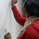 African American lady writes on white board in classroom