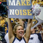 Cheerleader holding sign that says Make Noise