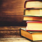 stack of books on the dark wood background. toning. selective focus on the middle book