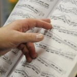 A hand pointing at sheet music.