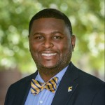 Bryan Samuel headshot. He is smiling, wearing a suit, with a very spiffy blue and gold bow tie.