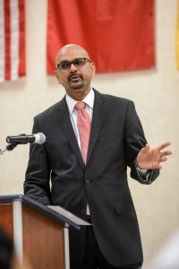 Davan Maharaj speaking behind a podium