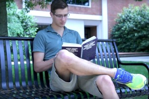 Student Patrick O'Brien reading on campus.