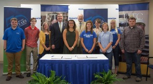 students and administrators at signing