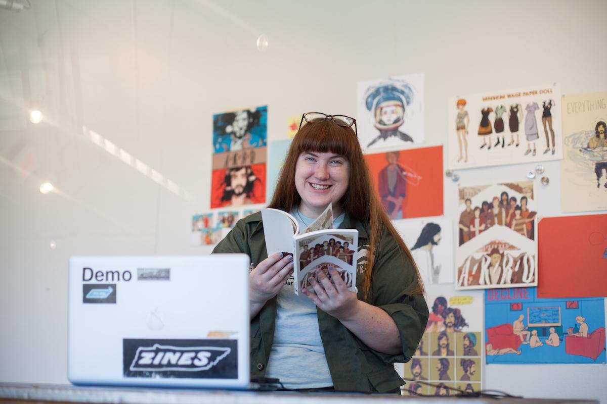 Tara Hamilton holding up her comic behind her laptop
