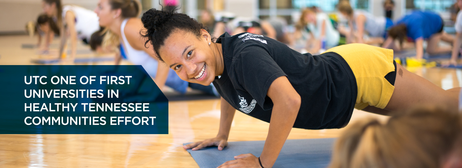 "UTC Student smiles for the camera while doing pushups in a Campus Recreation fitness class. ""UTC is one of the first Universities in Healthy Tennessee Communities effort"""
