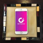 Photo of a smart phone displaying the Get Seated logo (a white G on a purple/pink background) laying on a plate with cutlery on either side.