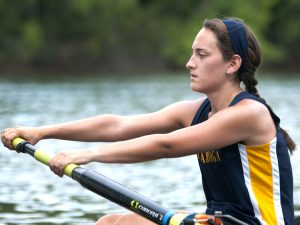 One of the members of the Women's Novice 4+ Rowing team at UTC giving it her all during a rowing competition.