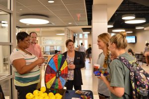Students stand in the Decosimo Success Center, spinning a multicolored wheel.