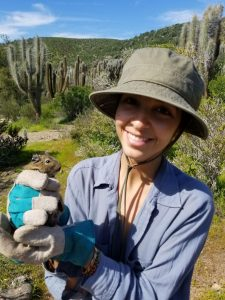 Grillo holds a 'goo ub her hands. There's a view of the parks landscape, with cactuses and shrubs behind her.