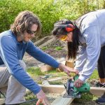 Students cutting wood to build outdoor recreation platform